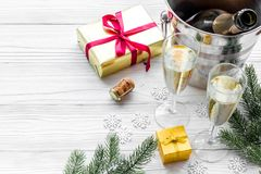Champagne for celebrate new year. Glasses, bottle in bucket, spruce branch on white wooden background copyspace Stock Photo