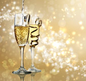 Champagne Celebration. Two champagne flutes on gold shiny background Stock Images
