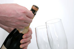 Champagne Celebration (8.2mp Image). Man's hand opening a bottle of champagne next to two champagne flutes shot on white stock photography
