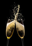 Champagne cheers. Glasses of champagne with splash, isolated on black background Stock Images