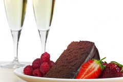 Champagne, Chocolate Cake Raspberries Strawberries. A plate of chocolate cake, raspberries and sliced strawberries with two flute glasses of champagne in the royalty free stock photos