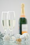 Champagne For Christmas. Two champagne glasses and bottle of champagne in background with Christmas decorations Stock Images