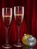 Champagne and christmas baubles. Two champagne filled flutes with two Christmas baubles on a red background Royalty Free Stock Photo