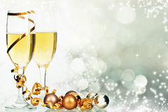 Champagne and Christmas decorations against holiday lights Royalty Free Stock Photography