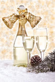 Champagne and Christmas decorations on golden background. Champagne in glasses and gift box on golden background Royalty Free Stock Photos