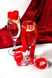 Champagne con il nastro ed il cuore rossi Fotografia Stock