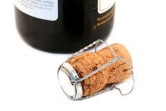 Champagne cork and bottle. A champagne cork and top alongside champagne bottle. Shallow DOF royalty free stock photography
