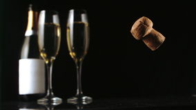 Champagne cork falling in front of two glass flutes and bottle. In slow motion