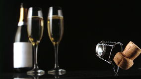 Champagne cork falling in front of two glasses and bottle stock footage