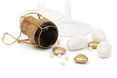 Champagne Cork and Wedding Favors. Champagne cork, with wedding favors or bonbonniere.  Sugared almonds, gold heart-shapes, and cachous.  Champagne glasses Royalty Free Stock Image