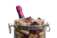 Champagne, Corks, Bucket. Detail view of a champagne bottle with a pink foil label in an ice bucket filled with corks pulled from many bottles. This is a festive stock photography