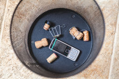 Champagne corks and mobile phone at bottom trash. Corks of sparkling wine and muzzle lie on the bottom of the wastebasket. Nearby is a broken cell phone stock photos