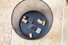 Champagne corks and mobile phone at bottom trash. Corks of sparkling wine and muzzle lie on the bottom of the wastebasket. Nearby is a broken cell phone royalty free stock photography