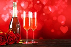 Champagne for couple in love in two flutes on table with red tablecloth stock photography