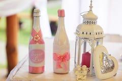 Champagne dans des bouteilles blanches se tiennent derrière une lanterne blanche avec du Re Images stock