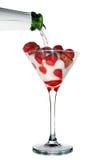 Champagne dat aan het glas met aardbei wordt ingeschonken Stock Afbeelding