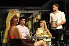 Champagne de boissons d'amis en café extérieur Image stock