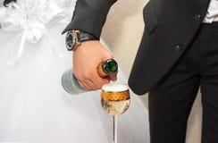 Champagne de derramamento em um vidro Foto de Stock Royalty Free