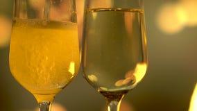 Champagne de scintillement se renversant dans la cannelure au-dessus du fond d'or de clignotement banque de vidéos