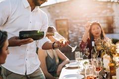 Champagne del servizio dell'uomo agli amici durante il partito Fotografia Stock