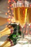 Champagne in den Gläsern, in der Flasche und in blured Leuchten lizenzfreie stockbilder