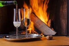 Champagne di versamento al camino accogliente Fotografia Stock Libera da Diritti