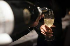 Champagne di versamento del cameriere nel vetro di vino in ristorante Immagini Stock