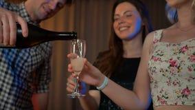 Champagne di versamento dell'uomo bello in vetri di due ragazze sexy video d archivio