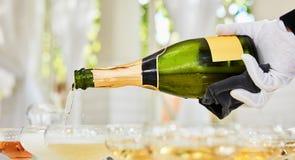 Champagne di versamento in flauto che stanno sulla tavola Fotografie Stock