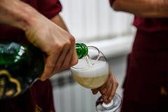 Champagne di versamento in vetro all'addio al nubilato, fine su immagine stock