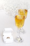 Champagne and diamond engagement ring. Glasses of champagne and diamond engagement ring with sparkle background Stock Photo