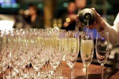 Champagne, die in Gläser durch Kellner am Ereignis gießt stockfotografie