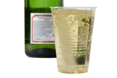 Champagne in disposable cup on the background blurred bottle of Royalty Free Stock Images
