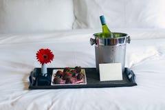 Champagne e fragole del cioccolato sul letto fotografia stock libera da diritti