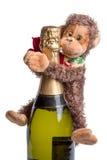 Champagne e giocattolo della scimmia Immagine Stock