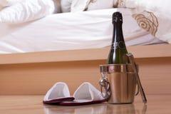 Champagne e sapatas perto de uma cama Fotos de Stock