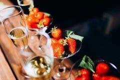 Champagne in een glas met aardbeien in nacht stock afbeelding