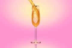 Champagne in een glas op roze achtergrond Royalty-vrije Stock Afbeeldingen