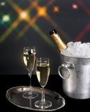 Champagne et seau à glace avec des lumières de fond Images stock
