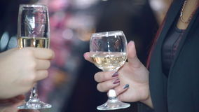 Champagne in Female Hands. Two girls talking and holding in his hand a wine glass with champagne stock footage