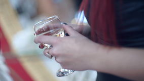 Champagne in Female Hands. Two girls talking and holding in his hand a wine glass with champagne stock video footage