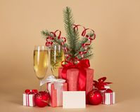 Champagne, fir-tree branch with tinsel, gift boxes Stock Images