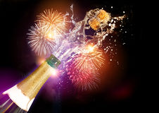 Champagne And Fireworks. A bottle of Champagne with it's cork popping during celebrations. A grand fireworks display adds to the atmosphere in the background Royalty Free Stock Image