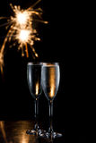 Champagne and fireworks. Dark scene with two glasses of champagne and fireworks in the background royalty free stock image