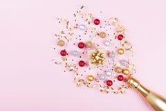 Champagne-fles met confettiensterren, giftdoos en vakantieballen op pastelkleur roze achtergrond Het patroon van Kerstmis vlak le royalty-vrije stock foto's