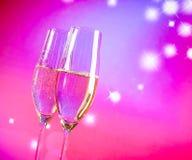 Champagne-fluiten met gouden bellen op blauwe en violette tint lichte achtergrond Stock Afbeelding