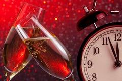 Champagne-fluiten met gouden bellen op de achtergrond van het Kerstmisrode licht bokeh met uitstekende wekker Royalty-vrije Stock Afbeeldingen