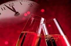 Champagne-fluiten met gouden bellen op de achtergrond van het Kerstmisrode licht bokeh met uitstekende wekker Stock Afbeelding