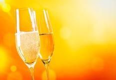 Champagne-fluiten met gouden bellen op gouden lichte achtergrond Stock Afbeeldingen