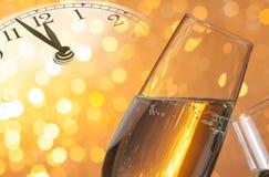 Champagne-fluiten met gouden bellen op gouden lichte bokehachtergrond Stock Foto
